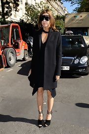 Carine Roitfeld looked ultra stylish in a boxy black coat layered over a handkerchief-hem dress during the Celine fashion show.