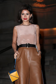 Miroslava Duma attended the Fendi after-party carrying a color-blocked cube wristlet from the brand.