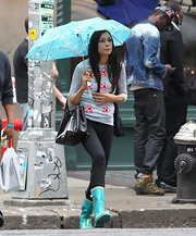 Famke Janssen walked in the rain wearing a quarter sleeved flower-adorned sweater, skinny jeans, and rain boots.