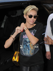 Miley Cyrus looked super cool in her gold cateye sunnies while out in London.