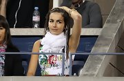 Camilla Belle watched the US Open wearing a fringed white scarf with a floral frock.