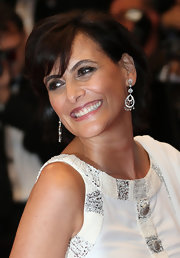 Ines de la Fressange attended the opening ceremony of Cannes Film Festival wearing a white long gown and diamond studded chandelier earrings to style it.