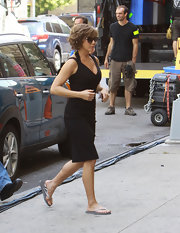 Jennifer Aniston knew how to stay comfy in between takes. She paired her elegant frock with silver flip flops.