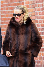 Sienna Miller paired classic Ray-Ban wayfarers with a faux-fur coat for a stroll in New York City.