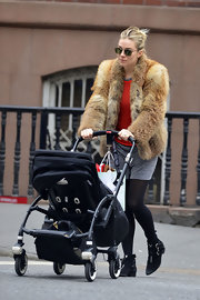 Sienna Miller did mommy duty in style wearing a thick fur coat.