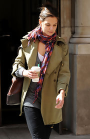Katie Holmes paired a plaid scarf by Madewell with an olive-green trenchcoat for a chilly day out.