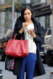 Famke Jannsen held coconut water in one hand and a roomy leather tote in the other while out for a stroll in Soho.