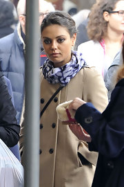 Mila Kunis paired a patterned scarf with a beige wool coat for a day out in Rome.