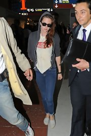 Kristen Stewart dressed down in gray espadrilles, jeans, and a hoodie for a flight.