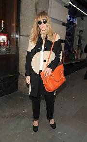 Suki Waterhouse complemented her outfit with a stylish ochre cross-body tote.