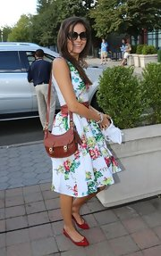 Camilla Belle teamed a red satchel with a floral frock for her US Open look.