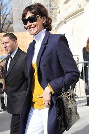 Ines de la Fressange protected her eyes with a pair of black sunnies at a Chanel fashion show.