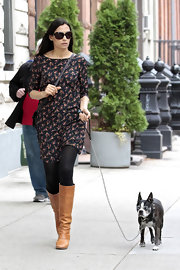 Famke Janssen walked her dog in NYC wearing a boatneck mini dress, black tights, and a pair of brown mid-calf boots.