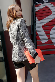 Lily Collins perked up her monochrome outfit with a neon-orange envelope clutch by Loeffler Randall.