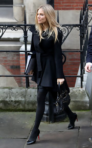 Sienna Miller was spotted outside the Royal Courts of Justice wearing a chic black peplum coat by Vidler & Nixon.