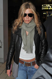 Jennifer Aniston jazzed up her airport outfit with an olive-green silk scarf.