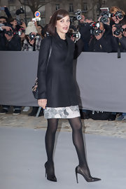 Marion Cotillard arrived for the Dior show wearing a fitted black jacket over a monochrome dress.